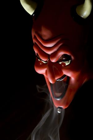Masque rouge du diable en fumée sur fond noir. Banque d'images