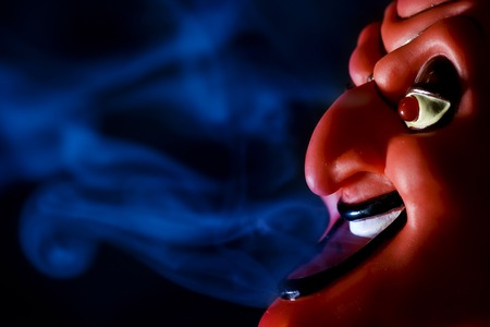 Red mask of devil in smoke on black background.
