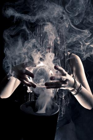 Belle sorcière flottant dans l'air. Pièce sombre de fond avec un fond noir. Des tresses afro sur ses cheveux. Chemise rouge.. Et fume autour.