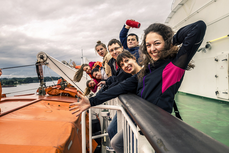 Group of young people is having fun on the deck. They are travelling around Norway. Stock Photo