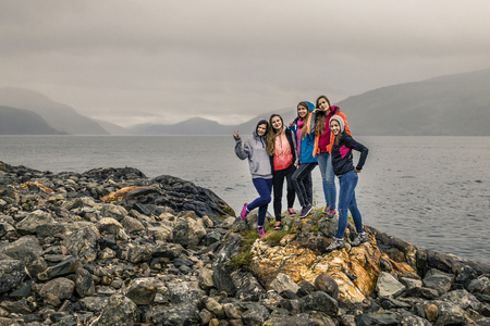 Group of attractive and funny girls on the stone near by fjord, Norway 免版税图像