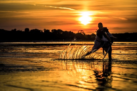 Silhouette of assassin with the sword at the beach. He is posing at the sea during beautiful, orange, yellow sunset. Splashes on the water from the sword. Фото со стока