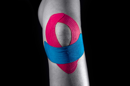 Medical taping for knee stabilization isolated on black background. Stok Fotoğraf