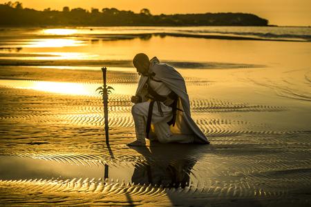 Ritratto di assassino in costume bianco con la spada al mare. Sta posando al mare durante il bellissimo tramonto. Giallo, luce soffusa.