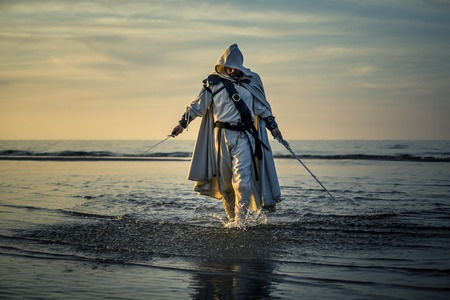 Portrait of assassin in white costume with the sword at the sea. He is posing near water during sunset, soft light. Stock Photo