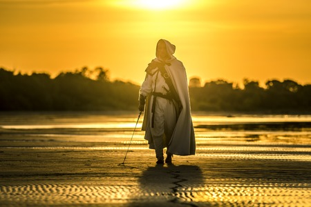 Portrait of assassin in white costume with the sword at the sea. He is posing at the sea during beautiful sunset. Yellow, soft light. 免版税图像