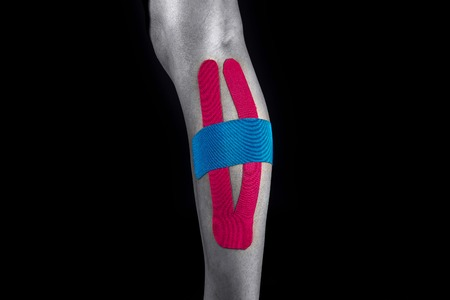 Medical taping for calf pain relief isolated on black background.