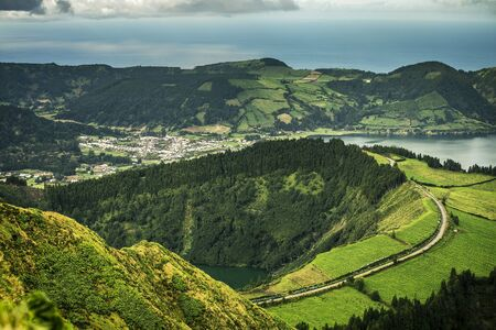 Aerial view on scenic landscape of volcanic lake Sete Cidades and green fields around it. Special shape of ground. Atlantic ocean on background. Azores islands, Sao Miguel, Portugal. Stock fotó - 128600825