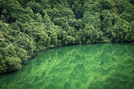 Aerial view from drone on volcanic lake and its coastline and forest near by it. Green forest and water in the lake. Reflections in the water. Top view. Azores islands, Sao Miguel, Portugal. Stock fotó