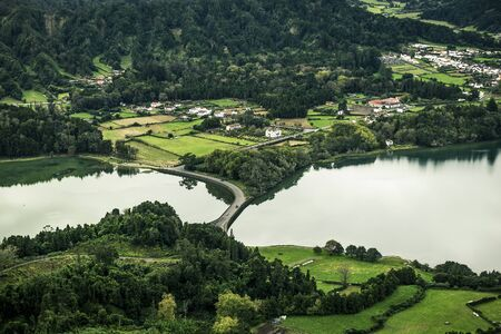 Aerial view on scenic landscape of volcanic lake Sete Cidades and the road separating the lake. Green field,  forest abd houses around the lake. Azores islands, Sao Miguel, Portugal.