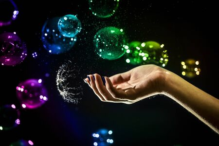 The transparent, iridescent soap bubbles isolated on black with elegant womans hand trying to touch them.