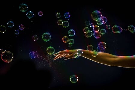 The transparent, iridescent soap bubbles isolated on black.