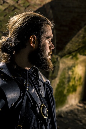 Portrait of assassin with long hair and huge beard close up standing in the ruined fortress.