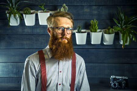 Portrait of bearded hipster with ginger hair in barbershop.
