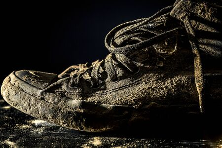Close up of very dirty sneakers fully in mud isolated on black background.