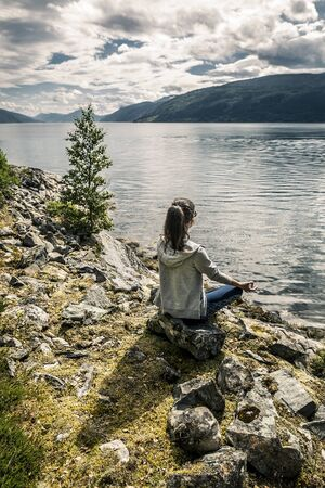 Young woman enjoying the sunny day on the fjord, Norway