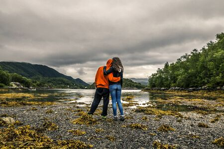 Happy couple during low water in Norway. Cloudy sky on background.