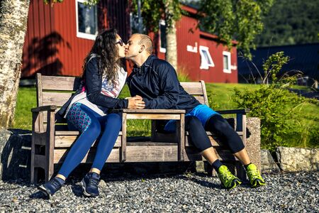 Happy couple sitting and kissing on the bench, Norway