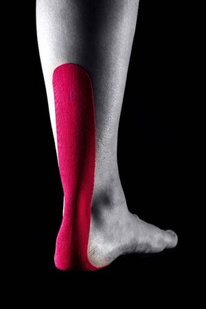 Medical taping for Achilles tendon showed on young model. Banco de Imagens