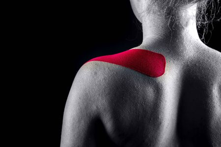 Medical taping for shoulder pain relief showed on young model.