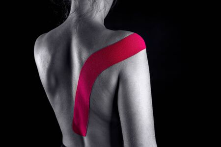 Medical taping for posture correction showed on young model.