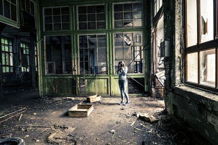 Chica joven en la vieja fábrica en ruinas está tomando una foto.
