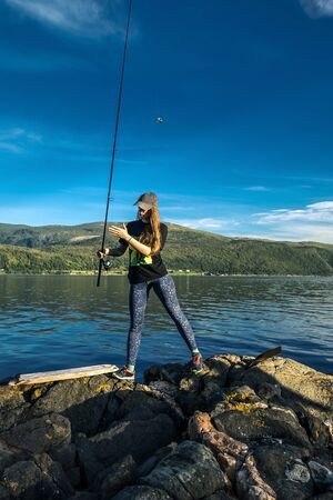 Young woman is fishing in Norway in the fjord. Banque d'images