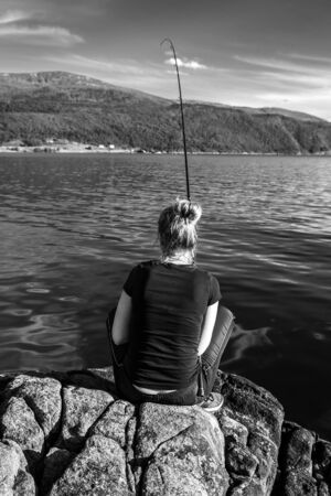 Young woman is fishing in Norway on the fjord. Banque d'images