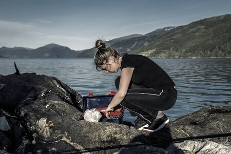 Young woman is fishing in Norway on the fjord.