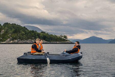Grupo de gente joven y atractiva en un barco con chaquetas de seguridad naranja va a algún lugar por el fiordo. Explorando lugares locales. Cielo nublado, Noruega. Foto de archivo