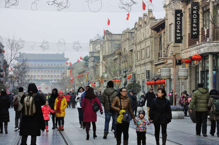 chinese dialect: Beijing, China - February 12, 2013: People in the commercial street at Qiamen during Chinas national day.