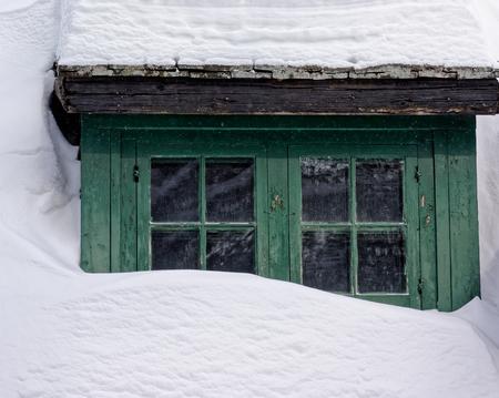 ウィンドウだけを示す深い雪に埋もれての丸太小屋 写真素材