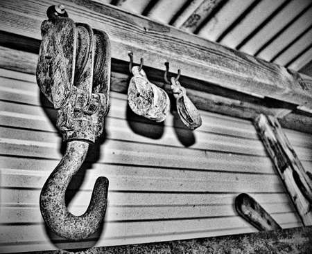 Rusty hooks and pulleys in a tin shed with noise in greyscale