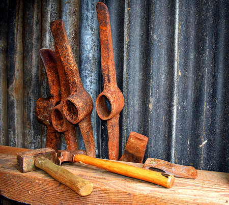 Rusty pick axe heads and a hammer in a tool shed Stock Photo