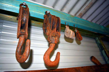 Rusty hooks and pulleys in a tin shed