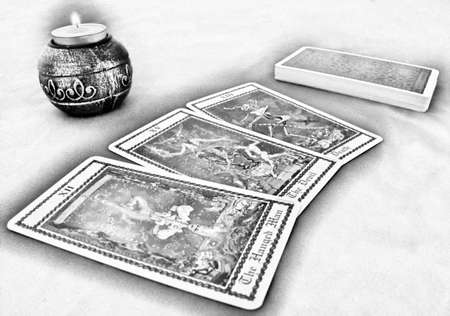 Three Tarot cards (The Hanged Man, The Devil, Death), deck and a candle on a table. Stock Photo