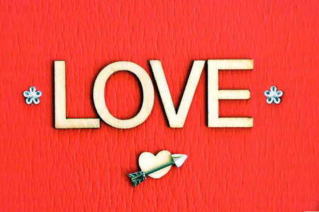 Wooden letter spelling 'LOVE' with an arrow, heart and small bouquet.