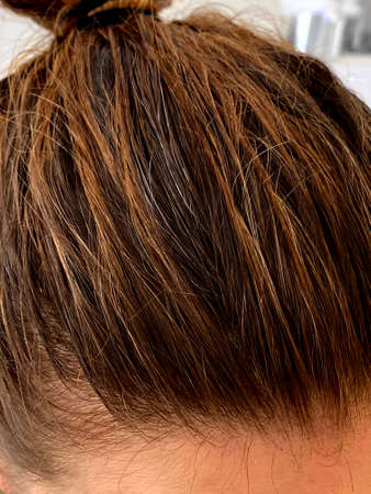 The top of a young woman's head with some new gray hairs showing