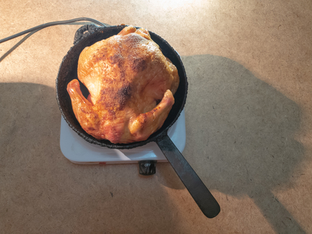 man turns a fried chicken in a pan on a hotplate.Cooking Fried Chicken