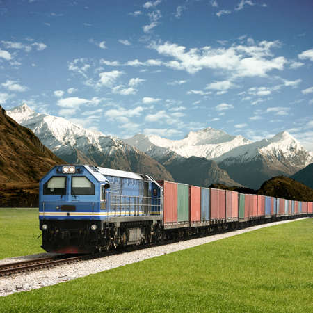 goods train: Freight Train in a Mountain Landscape Stock Photo