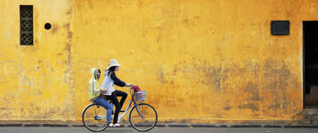 cycle ride: Two Girls on Bicycle with Old Wall in Vietnam