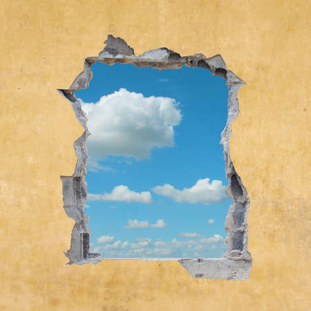 wall clouds: A Hole in a Wall with Blue Sky Stock Photo