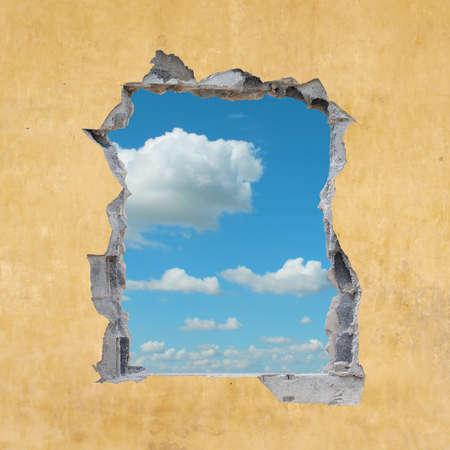 A Hole in a Wall with Blue Sky Foto de archivo
