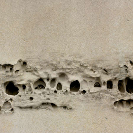 hole in wall: An Old Weathered Stone Wall with Holes Stock Photo
