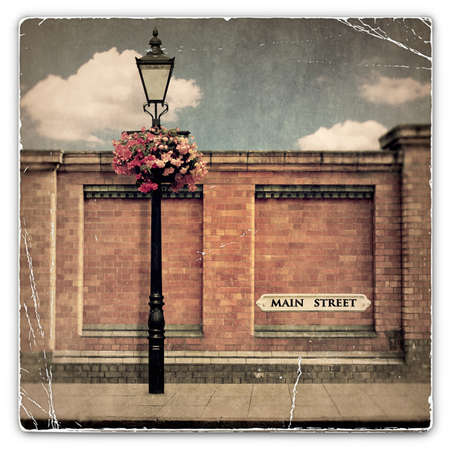 An Old Vintage Photograph of a Red Brick Wall with an Old Street Light and Main Street Sign photo