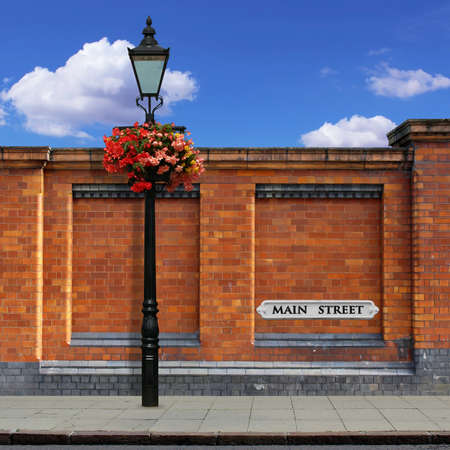 A Red Brick Wall with an Old Street Light, Main Street Sign and Sidewalk photo