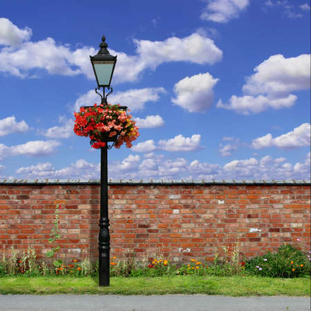 A Red Brick Wall with an Old Street Light and Blue Sky photo