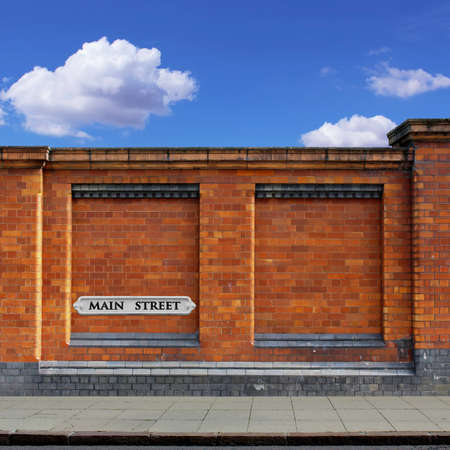 A Red Brick Wall with Main Street Sign and Sidewalk photo