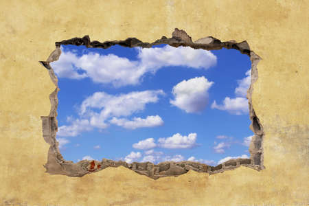 damaged: A Hole in a Wall with Blue Sky Stock Photo