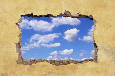 pared rota: Un agujero en una pared con el cielo azul
